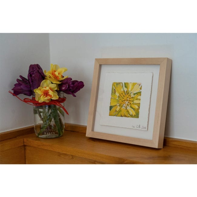 picture of the framed yellow flower original watercolor on a wooden shelf next to a jar with purple and yellow flowers inside it