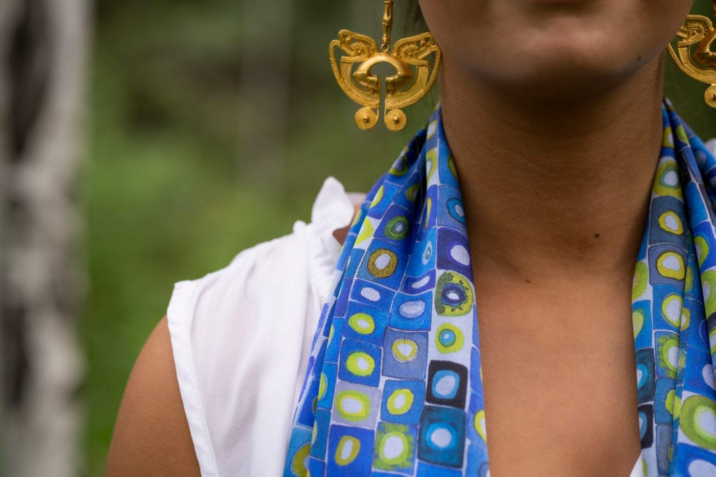 close up of woman wearing blue and green silk scarf with circles and squares