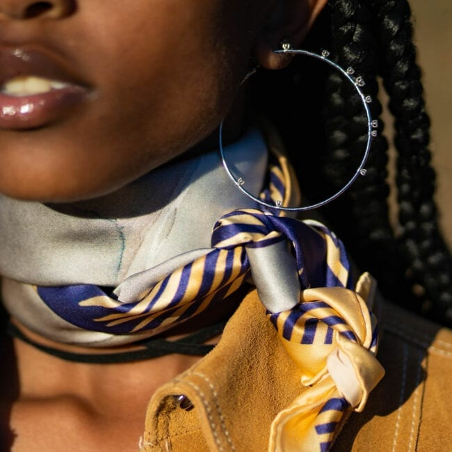 close up of young woman in suede jacket and hoop earrings wearing a scarf tied around her neck with blue and gold striped border