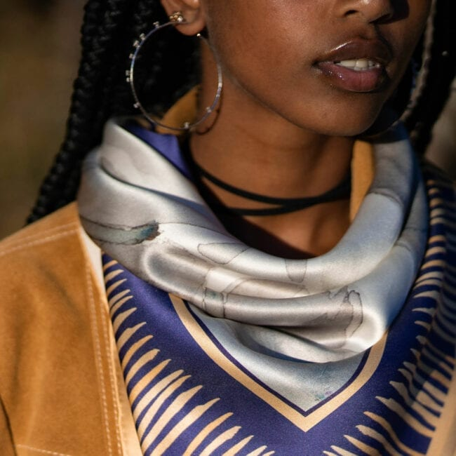 close up of a scarf tied around a young woman's neck with a triangle of blue and yellow abstract stripes