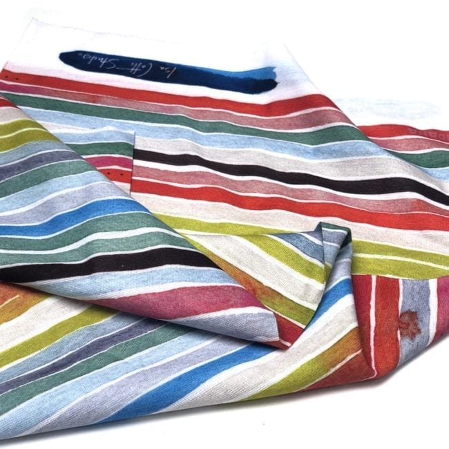neck gaiter with colorful stripes and watercolor mark with logo, laying scrunched up on a white background