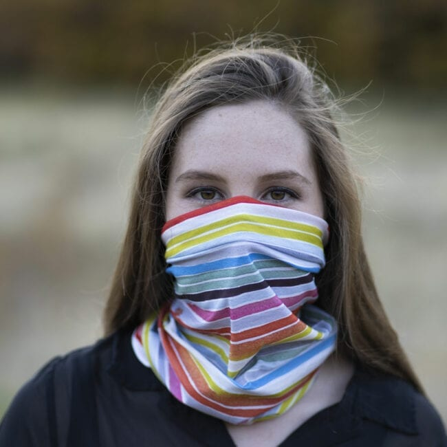 young woman looking foward wearing a colorful striped neck gaiter as a face mask