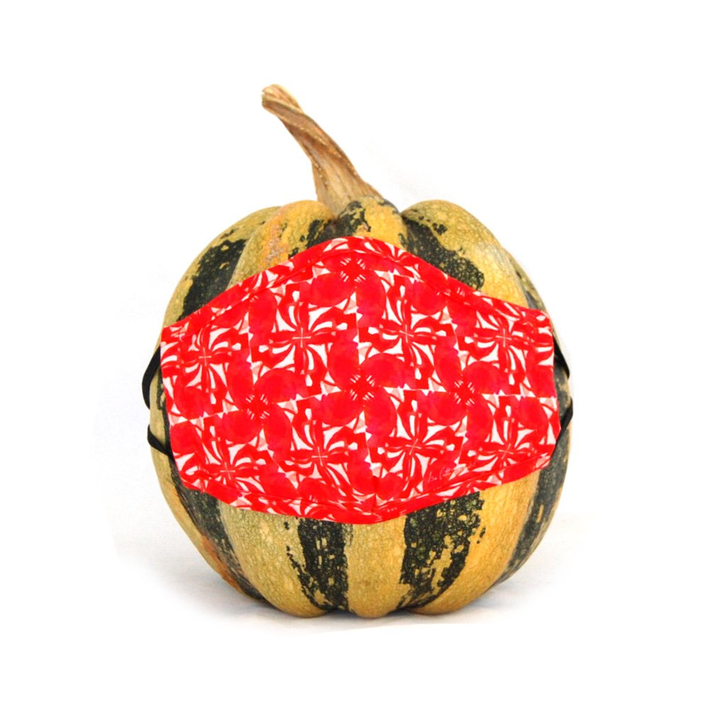 Vibrant poppy pattern turned int a pinwheel design printed on a cloth face mask. Face mask is displayed on a fall gourd