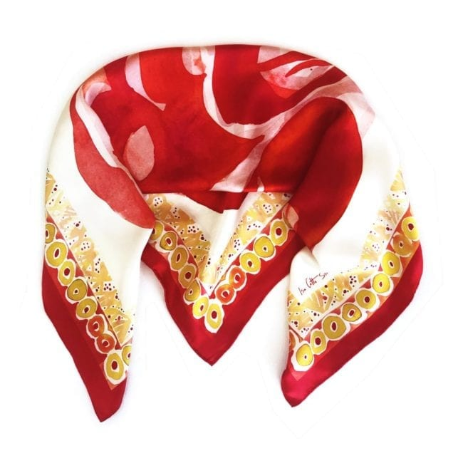 square silk scarf folded in half with corners pulled forward design is red abstract flower design in center and red and yellow dot border around the edges