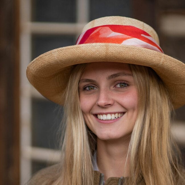 Smiling young woman wearing a straw hat with a red and white poppy scarf wrapped around the hat