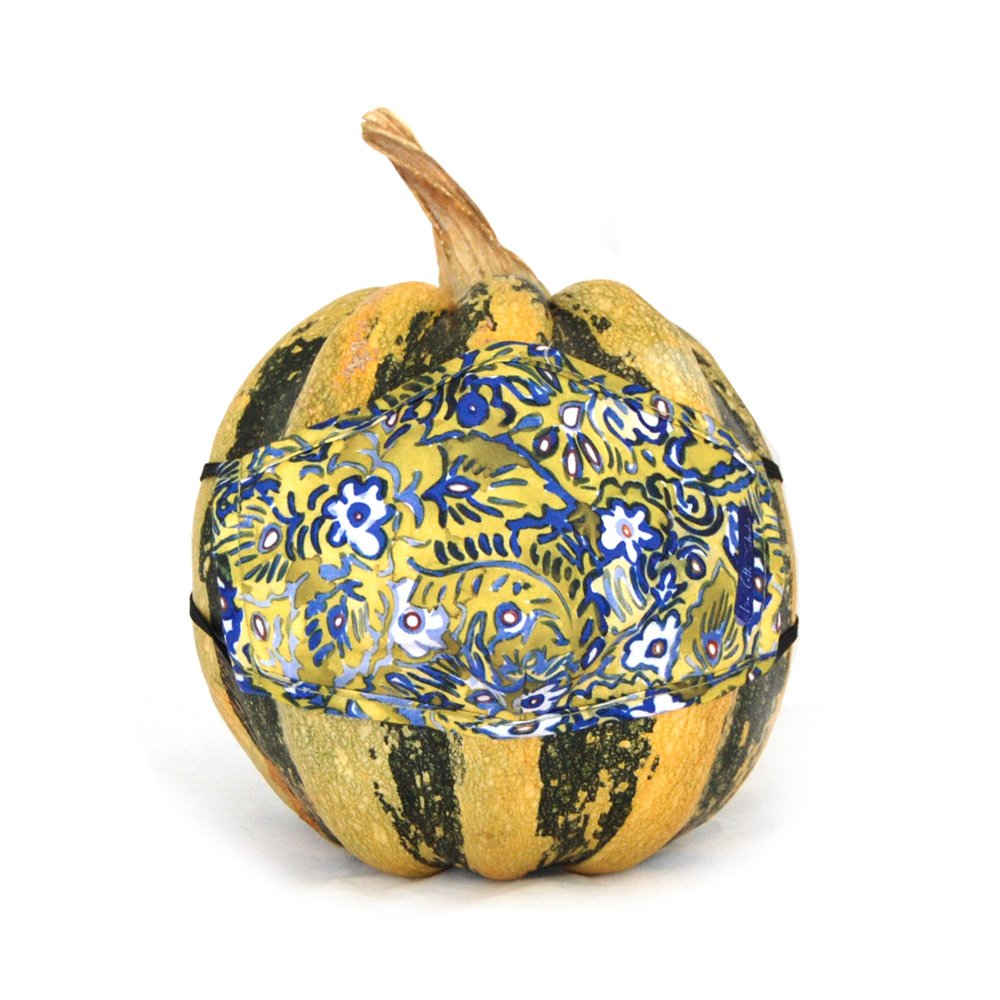 Face mask with green, blue and white floral design. Face mask is displayed on a fall gourd.