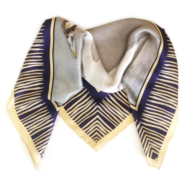 square silk scarf folded in half showing marsh yellow and blue border and abstraction of the painted whooping cranes
