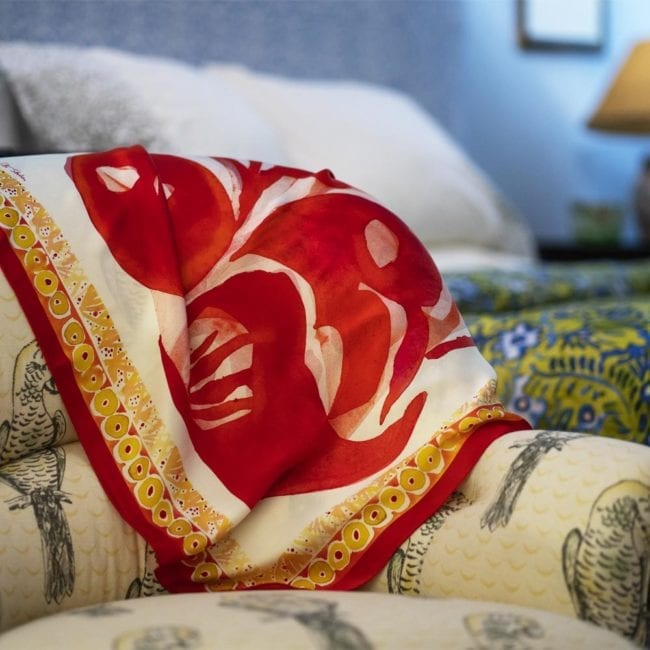 square silk scarf with red poppy design and yellow and red dot border draped on an armchair with a bed in background
