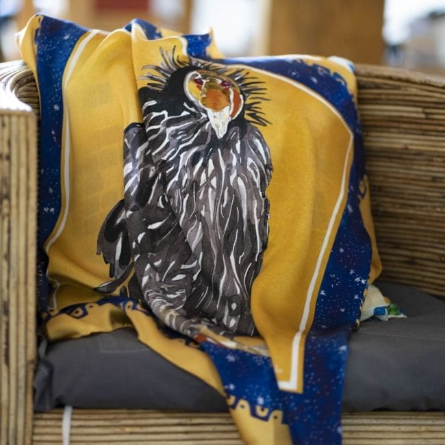 vibrant gold and blue silk scarf with painted California Condor in the center, scarf is draped over a chair