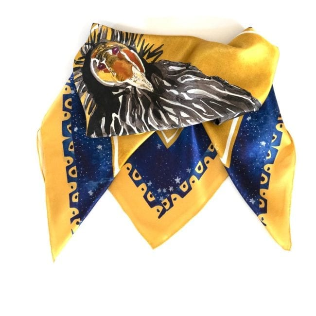 vibrant gold and blue silk scarf folded in a triangular shape that shows some of the California Condor painted in center of scarf