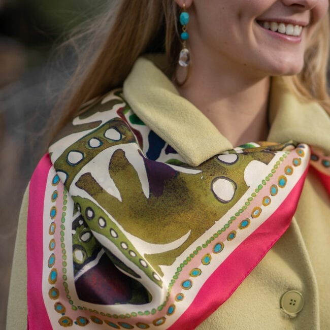 close up of young woman in a light yellow scarf with a pink and green scarf tied around her neck and draped over the side of the coat