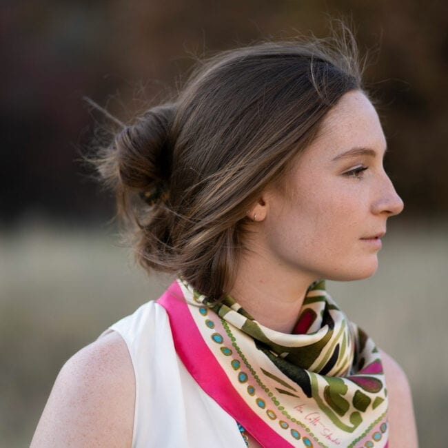 profile of young woman wearing a white sleeveless blouse with a pink and green floral scarf tied around her neck