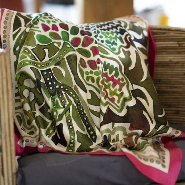 silk scarf featuring a painted green lady's mantle plant and vibrant pink border is draped over a chair