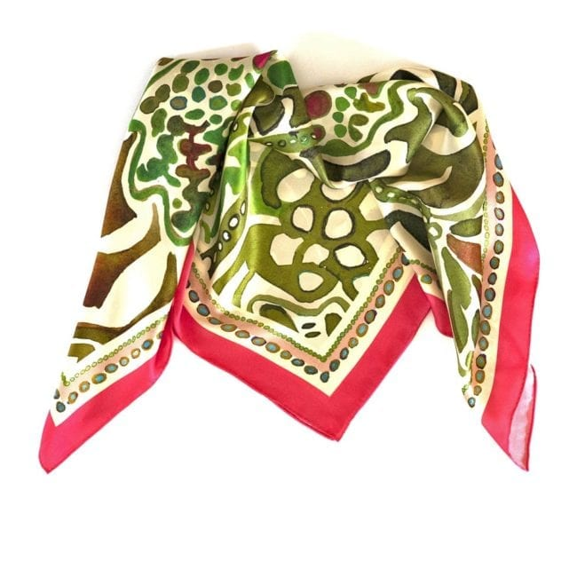 silk scarf folded into triangular shape, scarf features watercolor painting of green lady's mantle plant with a vibrant pink border