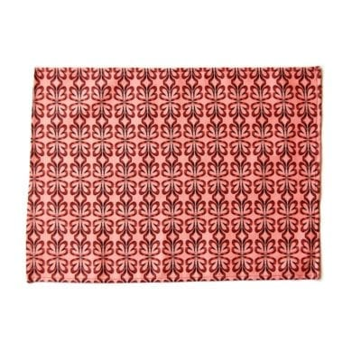 Pink cloverleaf print placemat on white background.