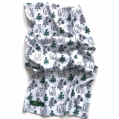 white microfiber neck gaiter with illustrated pattern of bear and evergreen trees