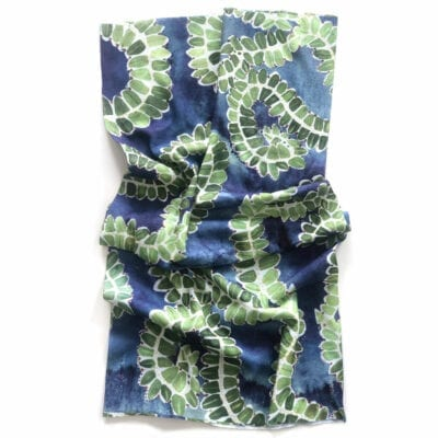 Neck gaiter with blue watercolor background with a green and white holly pattern