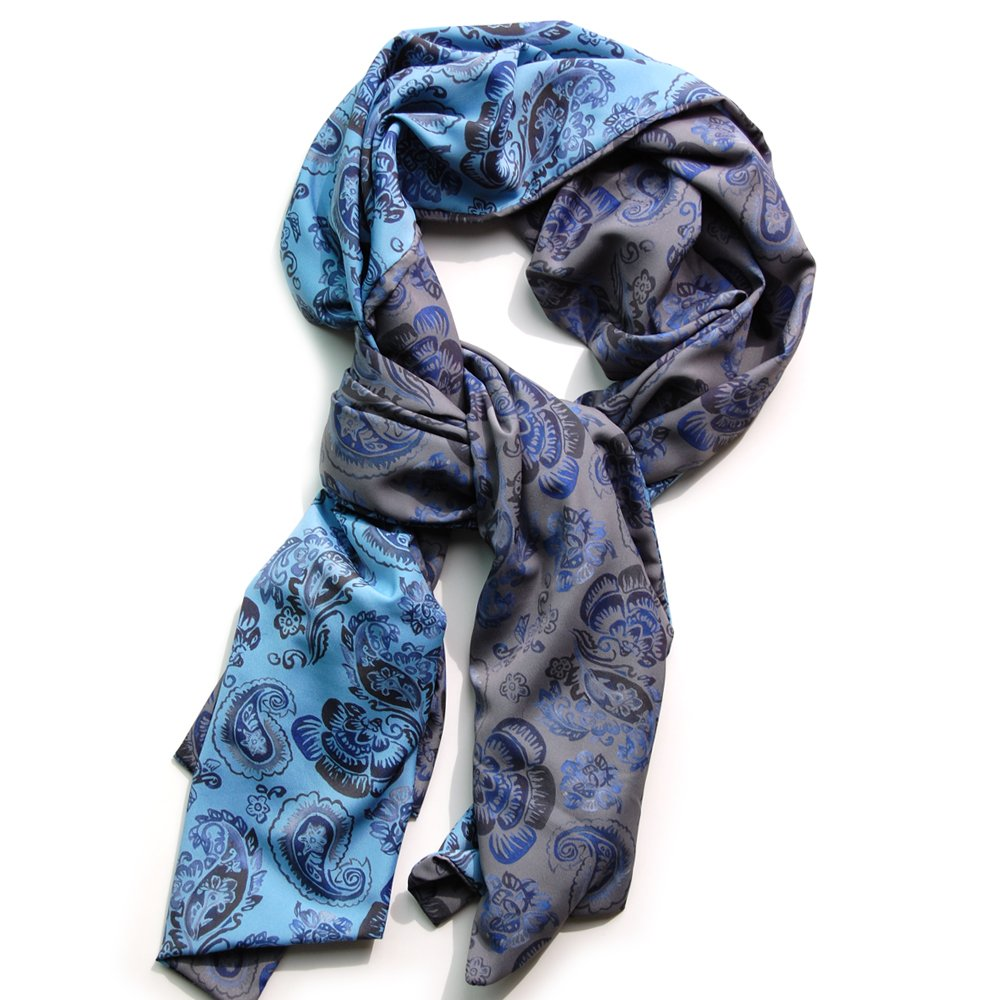 Reversible chiffon scarf with blue paisley pattern on one side and grey paisley pattern on the other. Scarf lying flat on white background, twisted so you can see both sides
