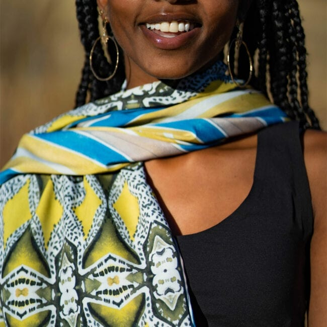 close up shot of young woman with organic blue green patterned scarf around her neck, the scarf is reversible and the backside is a geometric blue, green and white pattern.