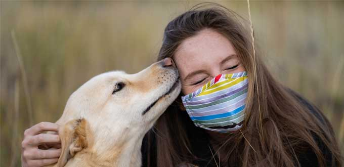 woman wearing striped face mask with dog licking face