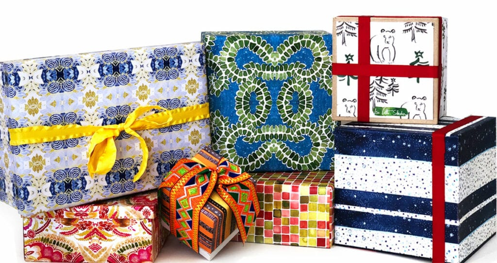 Stack of colorful wrapped gift boxes, all with a unique pattern and several with bows