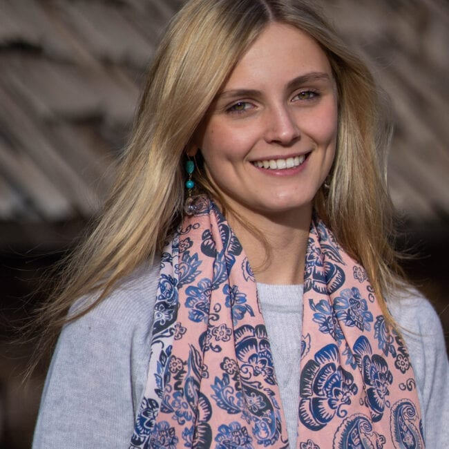 young woman with grey sweater and pink paisley scarf around her neck