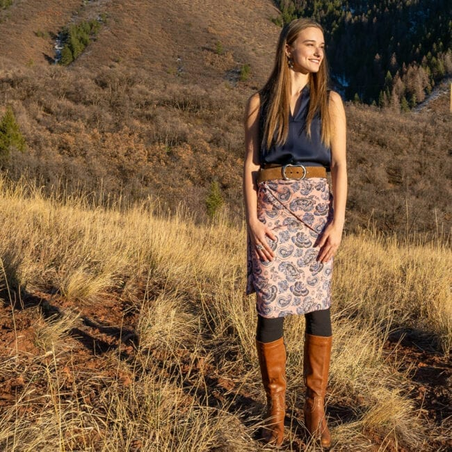 young woman standing on a fall hillside with black top and brown boots wearing an oversized reversible pink paisley scarf as a wrap skirt