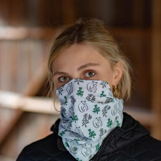model wearing neck gaiter with illustrated bear and clusters of evergreen trees.