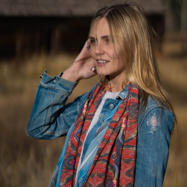 model wearing scarf with red bohemian pattern and elongated blue, white and grey stripes