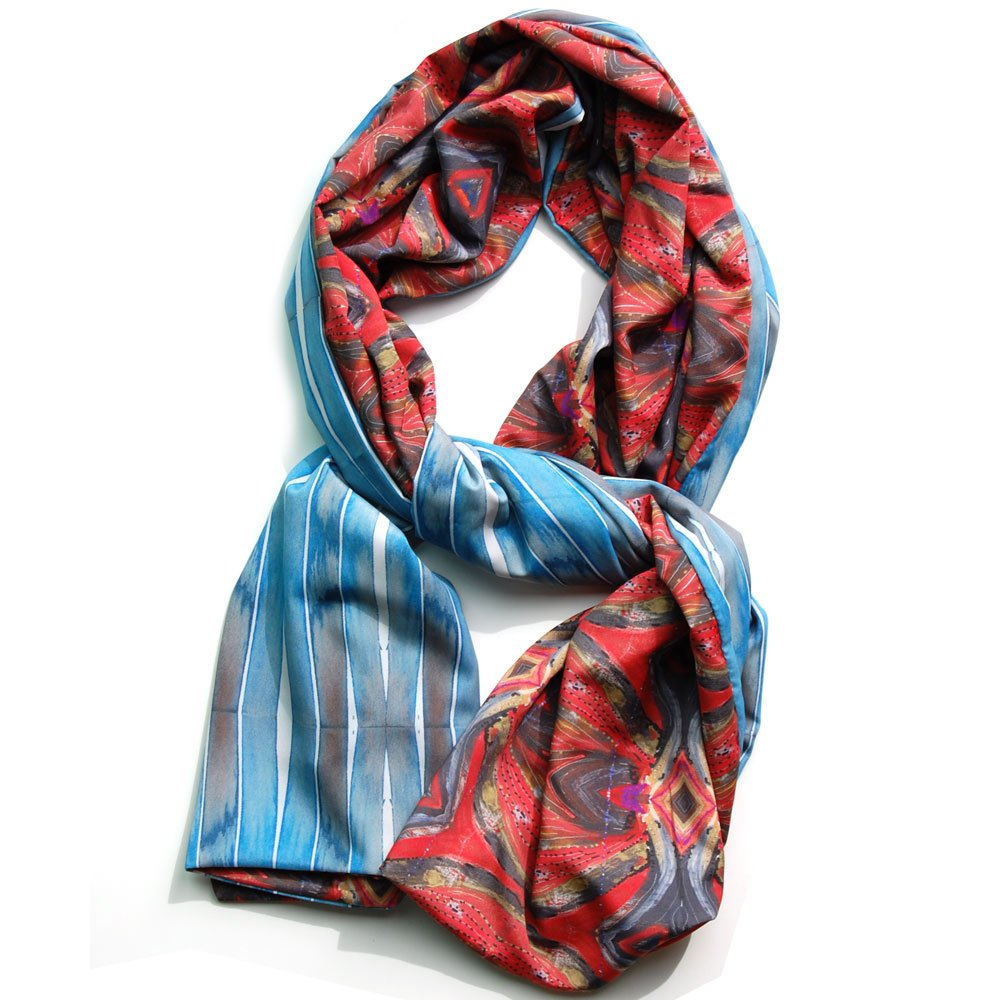 vibrant red bohemian patterned scarf with blue and grey striped pattern on the reverse side. scarf lying on a white background and twisted to see both sides of chiffon scarf