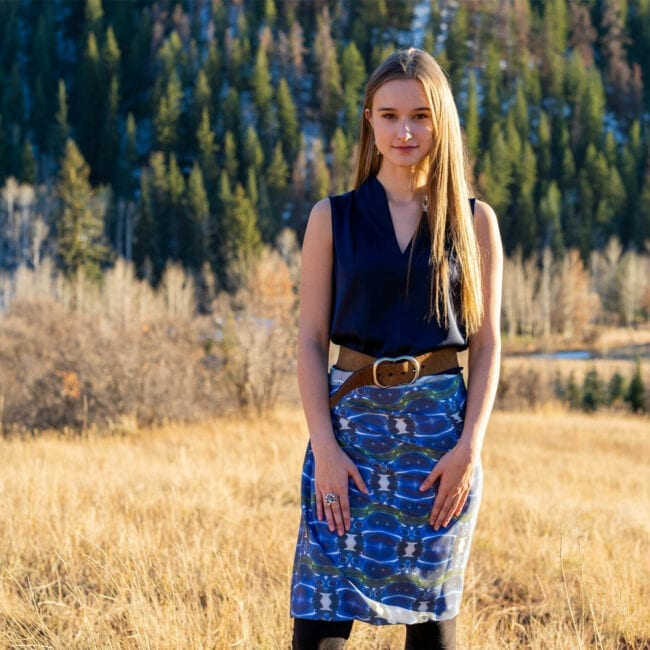 young woman standing in a fall mountain fields with evergreens behind her, wearing a blue green organic patterned oversized scarf as a wrap around her waist