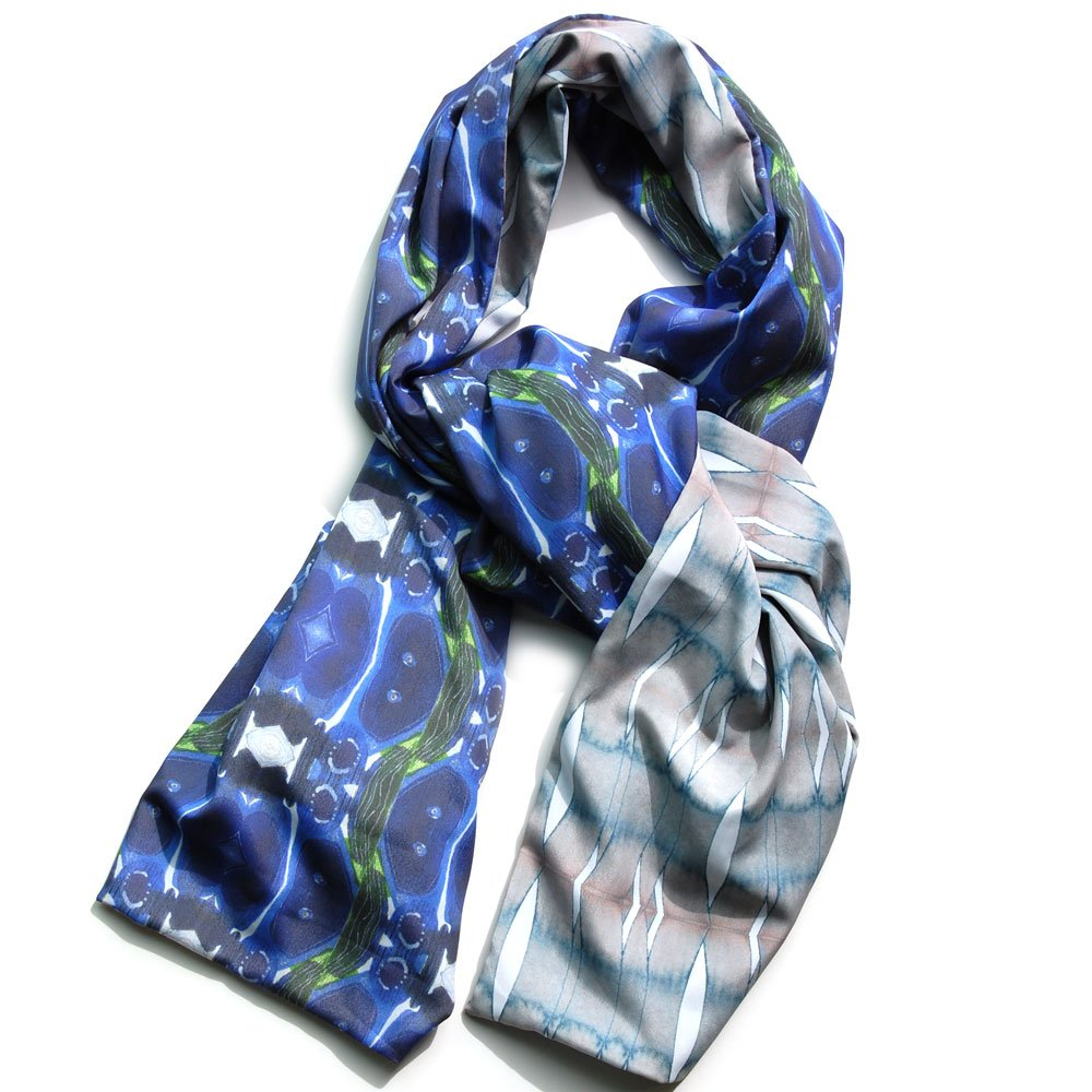 blue and green organic patterned scarf with a reversible striped pattern on the reverse in light green and blues. chiffon scarf is on a white background and twisted so you can see both sides of the scarf