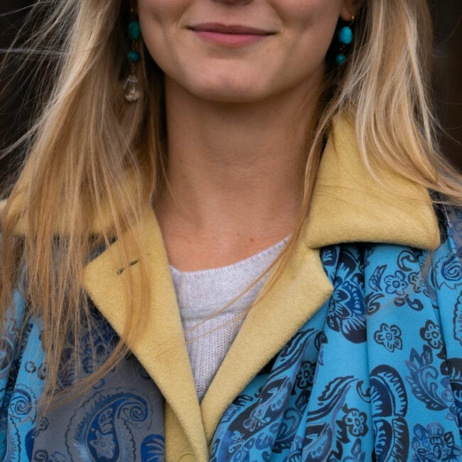 close up of young woman wearing a light yellow wool jack and a reversible blue and grey paisley pattern scarf under the coat lapels