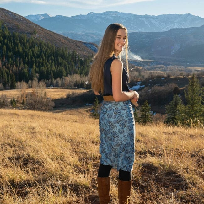 young woman standing in high elevation field with mountain range in background, wearing a blue and grey oversized scarf as a wrap skirt over her leggings