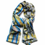 organic green and yellow patterned scarf with long geometric blue and yellow stripes on the reverse. scarf is lying on a white background