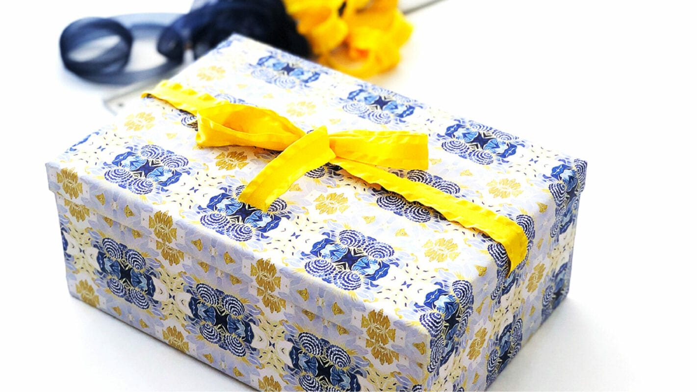 Finished tutorial image showing wrapped package with separate lid and bottom and yellow ribbon around the top. wrapping paper is a blue and white and gold kaleidoscope pattern.