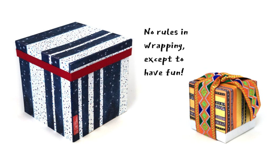 Tall gift box wrapped in blue and white striped paper with a red ribbon around the lid. Next to it is a small gift box wrapped in orange and yellow striped paper with a wide, bold orange and green ribbon.