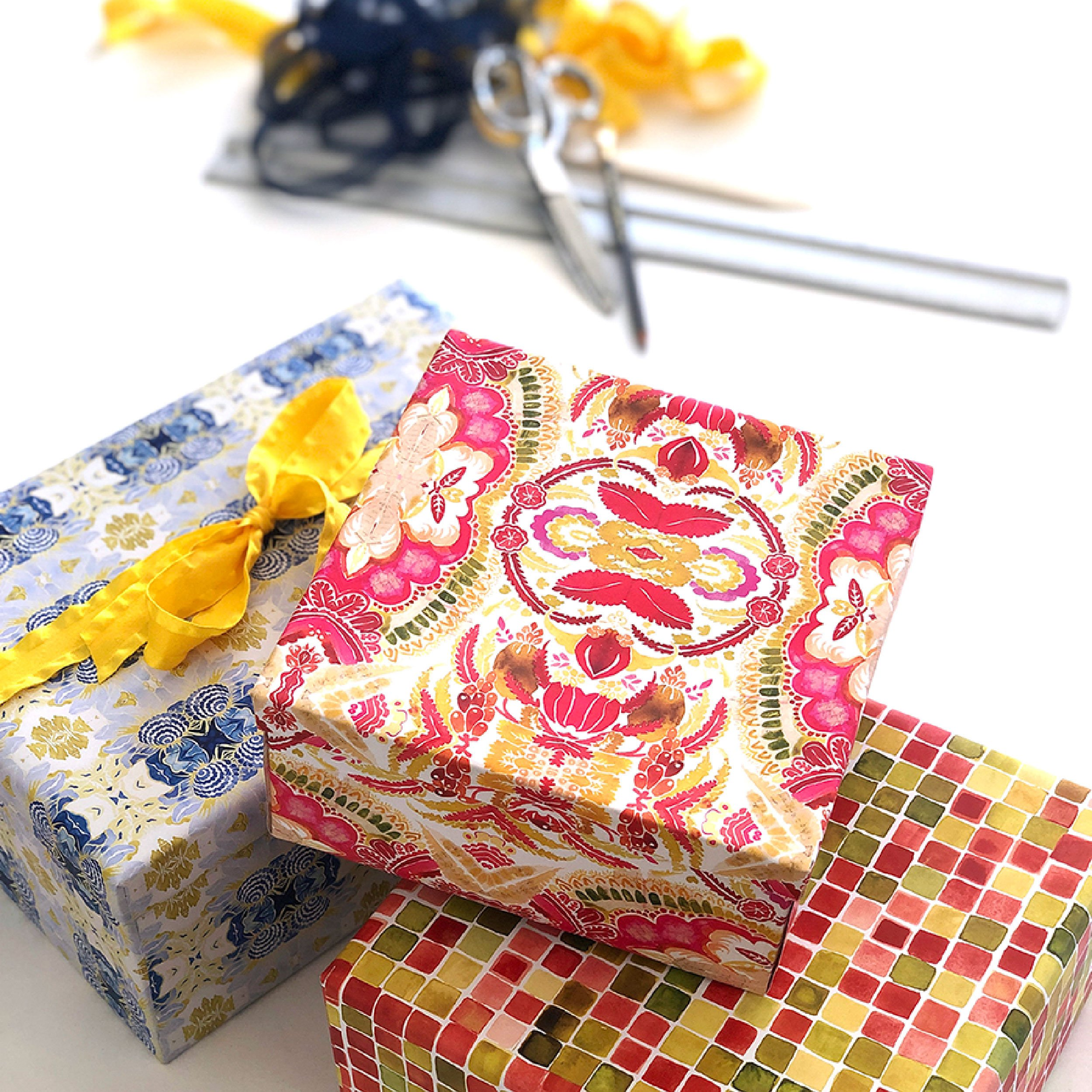 stack of wrapped boxes showing three new wrapping paper designs including a blue and white kaleidoscope design, a red and green square geometric design and a floral pink and green design