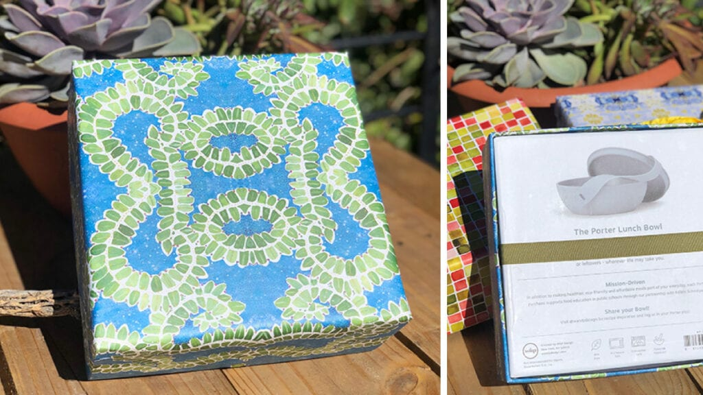 Wrapped gift box with blue background and green holly illustrated pattern. Box bottom shown with ribbon wrapped around.