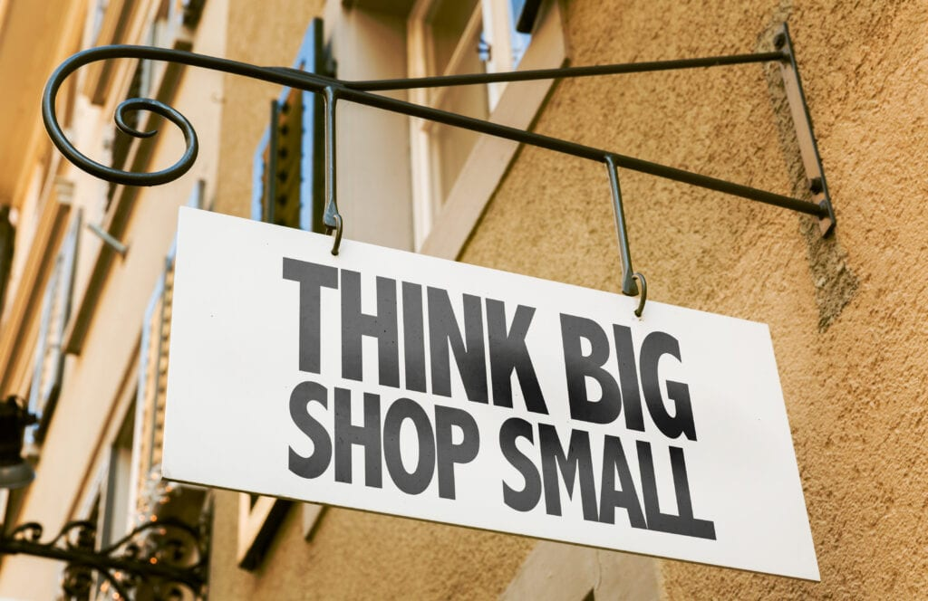 blade sign hanging from a shop that reads Think Big Shop Small