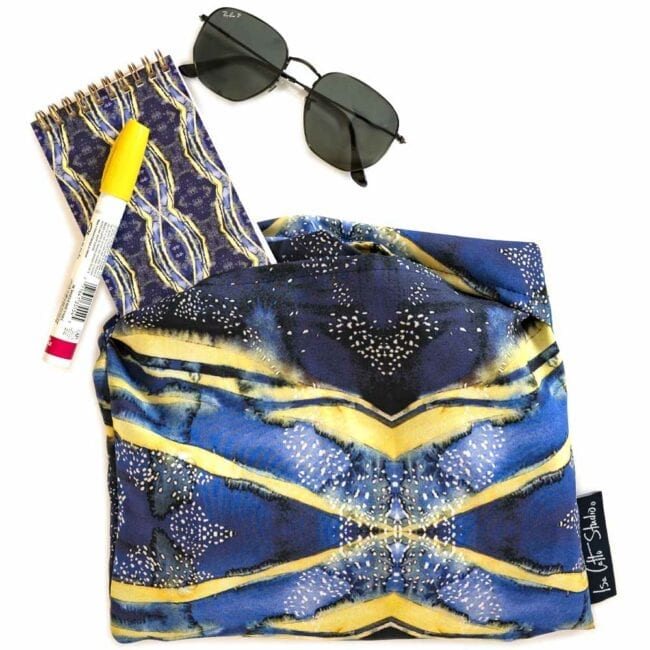 blue and yellow wrap in a matching bag with matching notebook, marker, and sunglasses