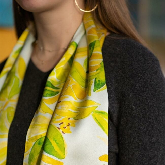 close up of a young woman wearing a light blue and green leaf patterned scarf