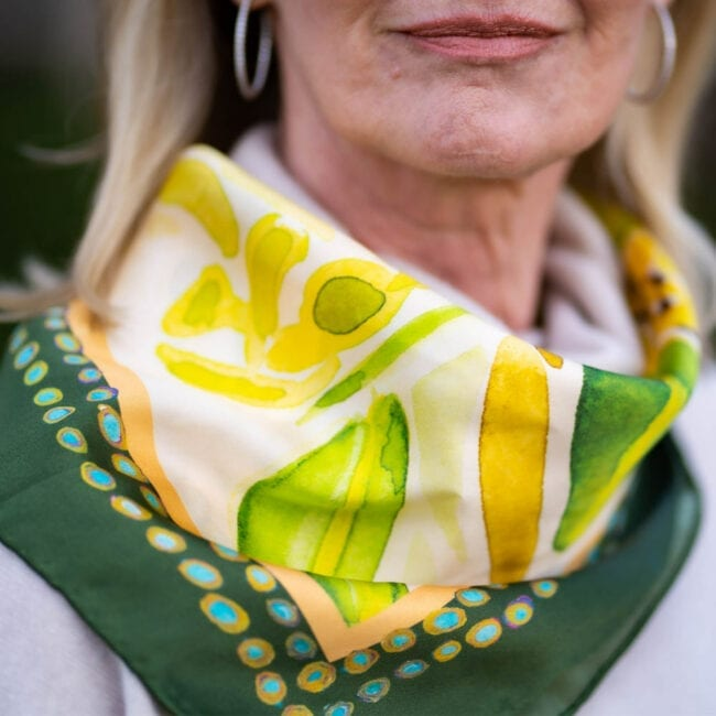 closeup of woman wearing green and yellow silk scarf tied around her neck