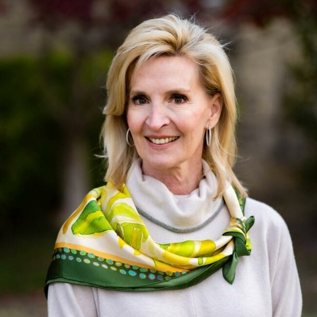 woman wearing green and yellow silk scarf tied around her neck