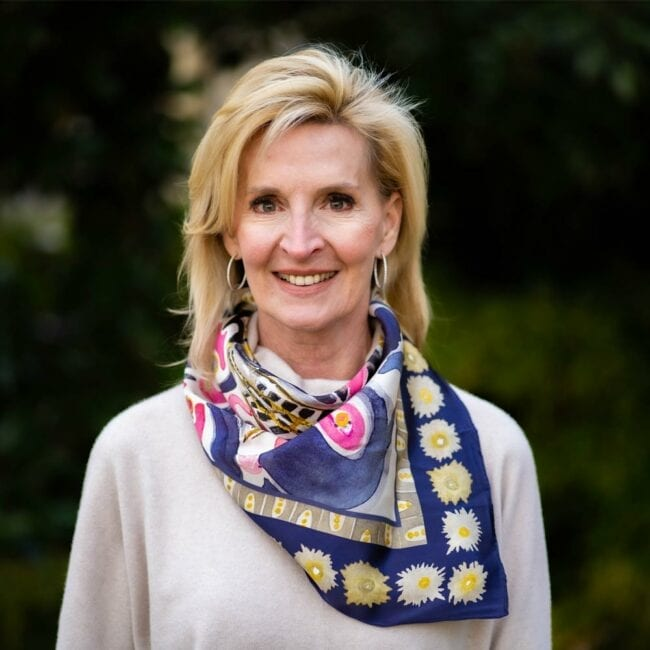 woman wearing purple, pink, and gold silk scarf tied around her neck