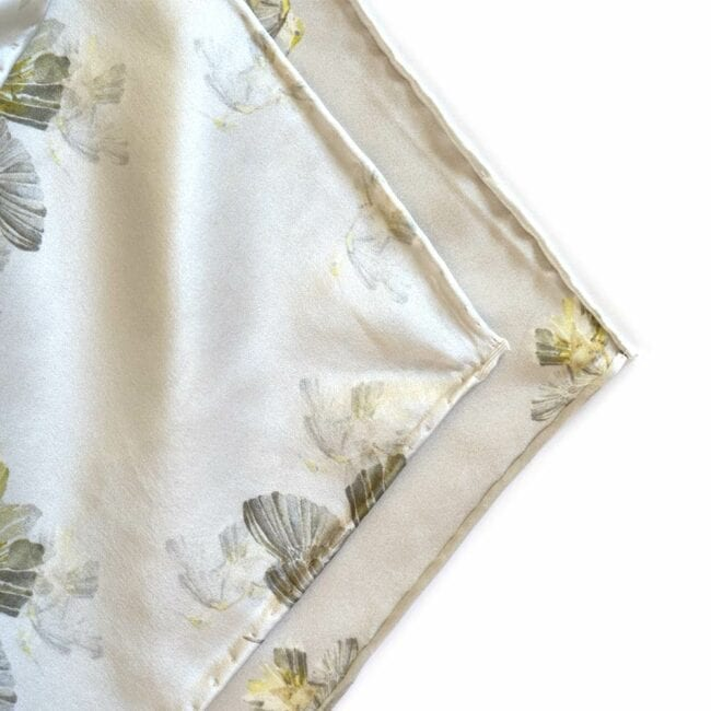 detail of a neutral gray silk scarf with hummingbirds on it