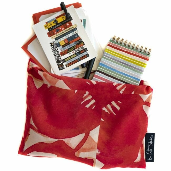 red floral pinwheel patterned wrap in a matching pouch with a striped notebook, notecards, and pens
