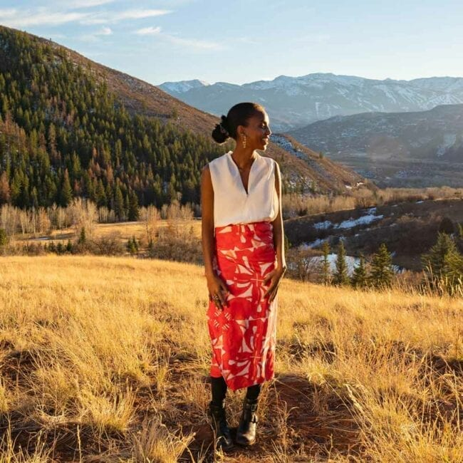 girl wearing red floral pinwheel patterned wrap with a mountainous backgroun