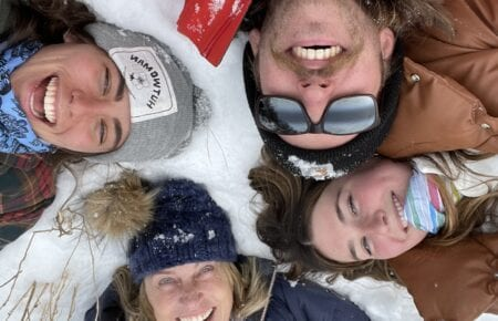 four people laying in the snow smiling