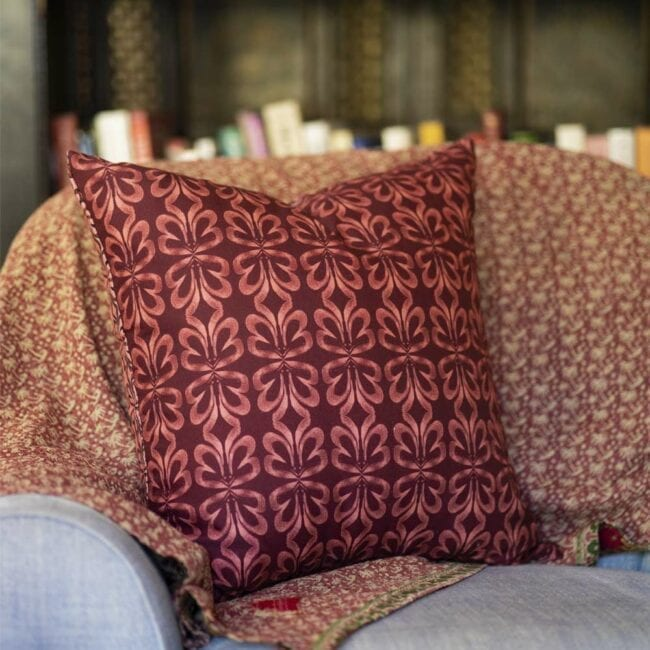 red clay botanical throw pillow on a chair in front of bookcase